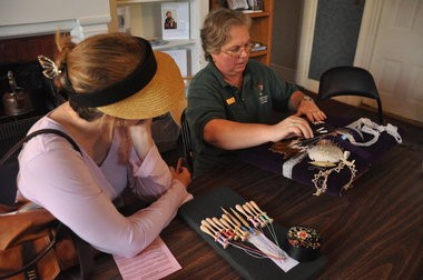 Tracy Hill (right), coordinator for the McLoughlin Memorial Association, gives a bobbin lace demonstration at the McLoughlin House.