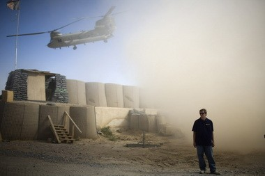 A U.S. contractor looks away from a dust cloud whipped up by a helicopter departing over the gatepost at Combat Outpost Terra Nova in Kandahar, Afghanistan in this July 2010 photo.