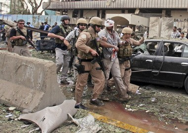Military contractors, including an injured American, leave the site of a massive bomb attack at the headquarters of the Baghdad provincial administration in Baghdad, Iraq in this October 2009 photo.