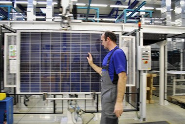 A worker in SolarWorld's factory in Freiberg keeps a watch on quality during the module assembly process, one of the last stages of solar module production.