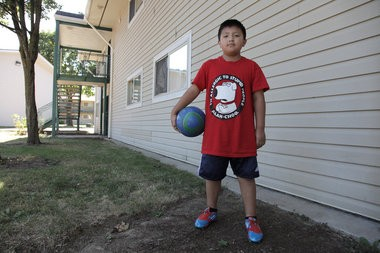 Jordan Soto, 8, poses with his Timbers Army donated cleats and soccer ball outside his apartment in the Tamarack public housing complex.