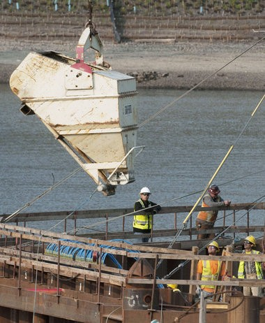 Concrete is lowered by bucket from a crane to be poured for the base of the eastern support of the Portland-Milwaukie Light Rail Bridge. The bridge will carry bikers, pedestrians, and light rail.