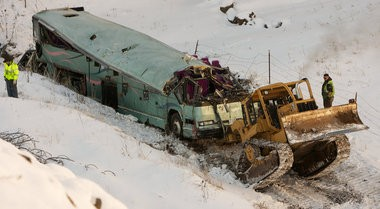 A piece of heavy equipment strains to move a bus that crashed Dec. 30, 2012, east of Pendleton, killing nine and sending multiple people to hospitals.