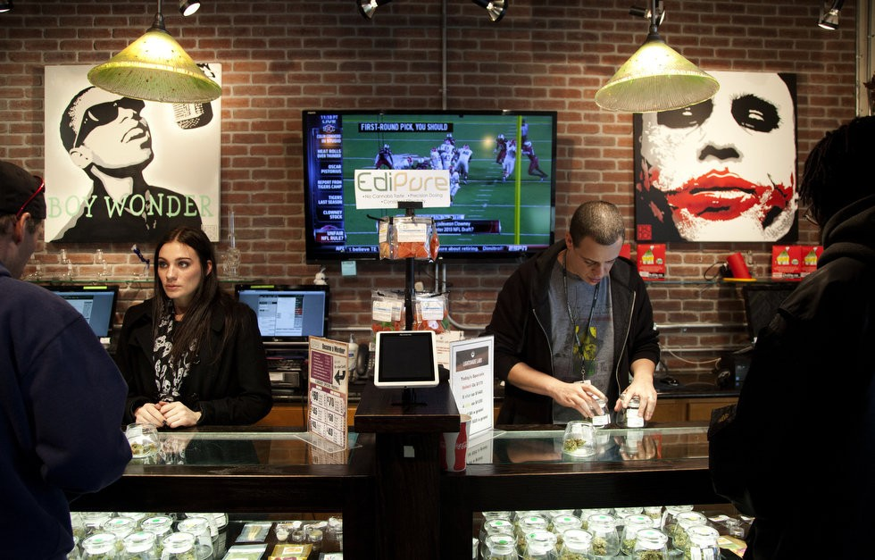 Jesse Herman, left, and Johnny Colbert work behind the counter at a brisk pace, helping medical marijuana customers at Lightshade Labs in Denver, Colo. Lightshade Labs features a retail dispensary at their site, which is a full service medical marijuana center. Beth Nakamura