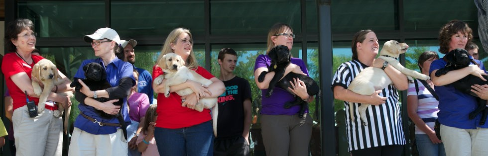 The staff at Guide Dogs for the Blind in Boring hold future possible guide dog puppies during a new puppy delivery ceremony in August.