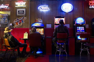 Martin Moen (left) of Vancouver and Tommy Dhomson of Salem play Oregon Lottery machines just before lunchtime at the Ace Tavern on Northeast Sandy Boulevard in Portland. The machines, considered among the most addictive forms of gambling, are the main source of revenue for the lottery.