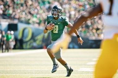 Oregon Ducks quarterback Marcus Mariota (8), runs in his second touchdown against the Wyoming Cowboys.