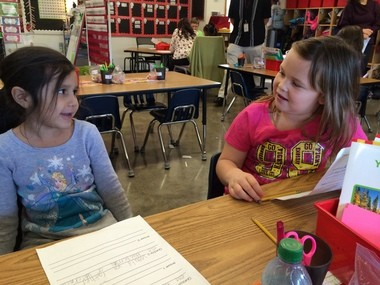 First-graders Lilyanna Baker, left, and Meegan Squally interview each other about their preferences: Turkey or ham? Watermelon or blueberries?