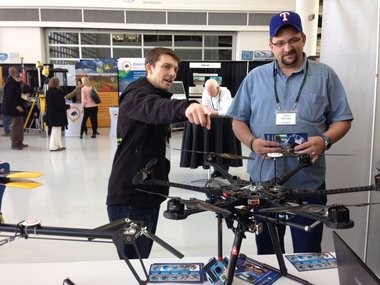 Stephen Burtt, pointing, left, CEO of Clackamas's Aerial Technology International, discusses his company's drone technology with an attendee of the 2014 Precision Farming Expo in Oregon.