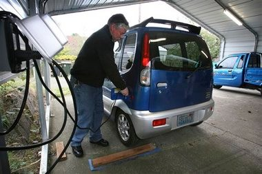 Joe Lambrix, founder of the nonprofit group Plug In Olympia, plugs in a Miles ZX40, one of his family's 100 percent electric vehicles, to charge at his home in Olympia. Owners of electric cars in Washington state don't pay gasoline or gas taxes, but the state is exploring a pay-as you-go system.