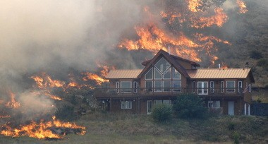 Flames surround a house on a hillside in August near Cle Elum, Wash. The Taylor Bridge fire blackened more than 36 square miles and destroyed nearly 100 structures.