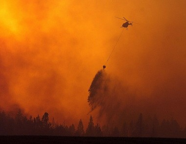 As the sun sets behind the plume of smoke, a helicopter makes a water drop on a fire Monday, Aug. 13, 2007, near Orofino, Idaho.