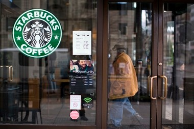 A customer walks into a Starbucks cafe in Washington, D.C. Starting Saturday, Starbucks will ban smoking within 25 feet of its cafes.