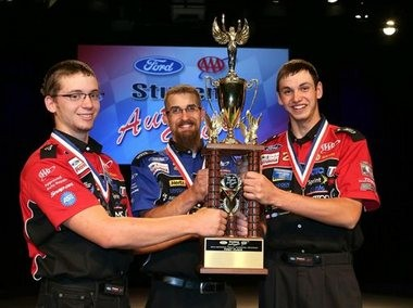 Logan Boyle (left) and Cody Collins (right), both from Vale High School in Vale, Ore., celebrate with instructor Drew Barnes after winning the national championship at the 64th Annual Ford/AAA Student Auto Skills Competition on Tuesday at Ford World Headquarters in Dearborn, Mich. The teens beat teams from 49 other states as they successful carried out repairs on a 2013 model Ford Explorer XLT.