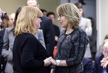 """Former Arizona Congresswoman Gabrielle Giffords, right, greets Cheryl Stumbo, who, like Giffords, survived being shot, after both testified before a Washington state House panel Tuesday, Jan. 28, 2014, in Olympia, Wash. Giffords, who survived a 2011 shooting, testified before the panel considering an initiative to expand firearm background checks in the state, telling lawmakers that """"the nation is counting on you."""" Stumbo was one of six women shot, one fatally, in 2006 at the Seattle Jewish Federation."""