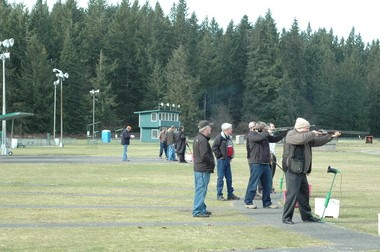 Sen. Don Benton (wearing a beanie), R-Vancouver, shoots at a clay pigeon. Rep. Luis Moscoso (wearing a black trench coat), D-Mountlake Terrace, watches as another member of his group takes aim.