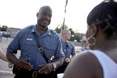 Missouri Highway Patrol Capt. Ron Johnson meets with residents while walking the streets of Ferguson, Mo., on Aug. 19, 2014.