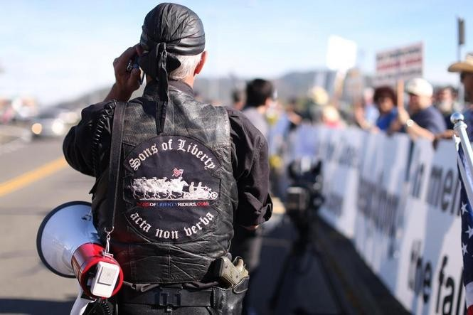 A biker shows off his handgun while joining the crowd waiting to protest Pres. Barack Obama's visit to Roseburg to meet with families of victims of the Umpqua Community College shooting.