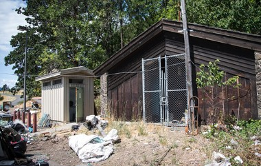 An electric cord stretches from a shuttered restroom, allowing residents access to power at the Underwood site. The smaller structure is the restroom shared by the camp's residents.