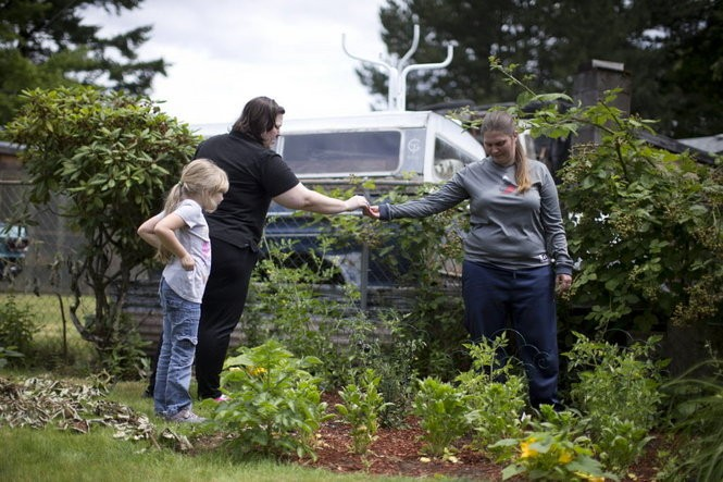 Anastasia, left, Rachel and Laurel spend time in the family's backyard garden. June, 2016 Beth Nakamura/Staff