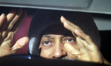 Bhagwan Shree Rajneesh gestures to his disciples during his daily drive at Rancho Rajneesh.
