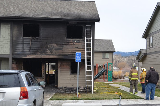 Firefighters survey the damage of a Nov. 30, 2017 fire that killed two sisters in Prairie City. Their deaths went unacknowledged for 350 days until the Department of Human Services disclosed that case workers had interacted with the girls' family 10 times since 2012, the final time two months before they died. Credit: Blue Mountain Eagle