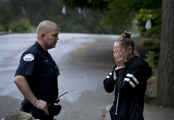 Officer Evin Eustice of the St. Helens Police Department talks with a woman whose family member was suffering a crisis. (Photo by Beth Nakamura)