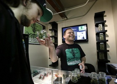 Vendor Jeff Simmons, right, smiles as he holds up a jar of marijuana for Dylan Tracy to sniff during the grand opening of the Seattle location of the Northwest Cannabis Market, for sales of medical marijuana products, Wednesday, Feb. 13, 2013. Voters in Washington state last fall passed Initiative 502, which legalizes the recreational possession of up to an ounce of marijuana and calls for the creation of state-licensed pot growers, processors and retail stores. Pro-legalization advocates in Oregon hope state lawmakers will approve a bill to legalize and tax the drug.