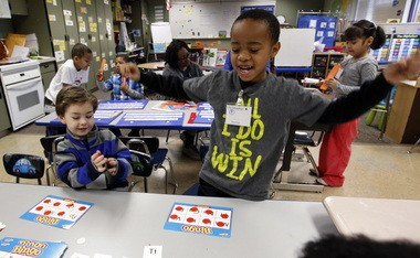 In this Feb. 6 photo, Christopher Larry, Jr., right, reacts to winning a letter bingo game as Joel McCain looks on in their kindergarten classroom at Campbell Hill Elementary in Renton, Wash.