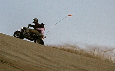 An adult and child climb a dune during Dunefest at Winchester Bay