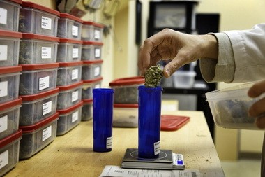 Michael Fowler, a volunteer at the Human Collective in Tigard, dispenses marijuana from their apothecary.
