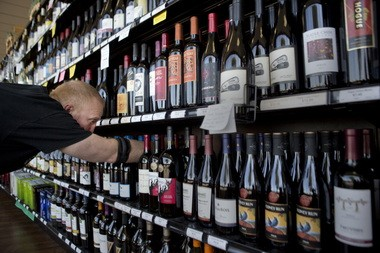 Hollywood Beverage general manager Troy Osburn stocks the wine section Thursday of the combined liquor-beer-wine shop. The state liquor outlet was given special permission last year to add beer and wine to its shelves. Now all liquor stores may do the same.