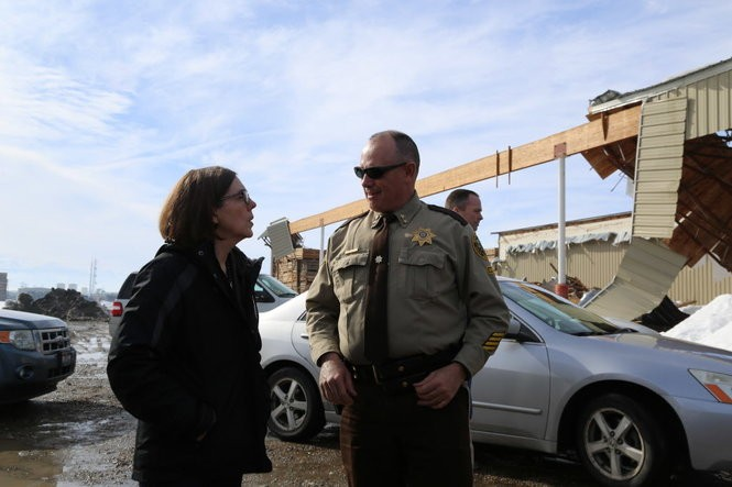 Gov. Kate Brown talks to Malheur County Sheriff Brian Wolfe in front of a collapsed building near Ontario. Brown got a call early Feb. 9 that the Eastern Oregon city and surrounding communities needed help responding to damage from heavy snow. She dropped everything and, on Feb. 10, went there to try to bring attention and emergency resources to their needs.