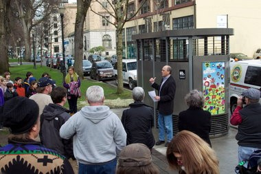 City Commissioner Randy Leonard helps christen a Portland Loo at Northwest Couch Street and Eighth Avenue. Children and staff from the nearby Emerson School help with The First Flush.