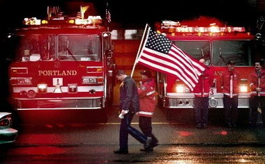 A Portland police officer and firefighter lead a procession down S.W. Naito Parkway on New Year's Day 2002.