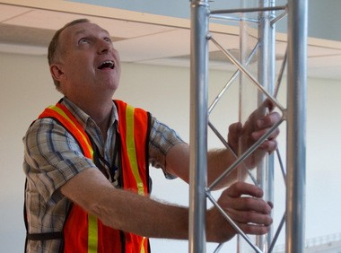 A giant barometer, which is used to measure atmospheric pressure, is being built in the Engineering Building at Portland State University. Tom Bennett, who works in the civil and environmental engineering school, positions glass tubing used in the project.
