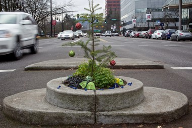 """A Charlie Brown occupation: Mill Ends Park, the world's smallest city park at 2 feet in diameter, shows its holiday colors Friday, Dec. 23, 2011 -- on the tree that was stolen within the past week. It still displays remnants of its Dec. 16 """"occupation"""" by a flash mob of Occupy Portland demonstrators in which one person was arrested. The occupiers stuck tiny protest signs into the soil, such as """"You can't evict an ideal,"""" and ringed the concrete perimeter with plastic toy soldiers and tiny tents. The signs are gone, but the soldiers and tents remain."""