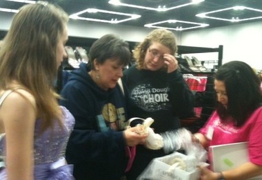 Kathryn Jacobson, left, helps her mother Grace Jacobson and volunteer Terry Williamson, far right, put a pair of high heels from Abby's Closet into a box as friend Larissa Schuermyer looks on.