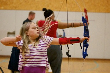 The wind from the release of her arrow and bow string pull up 10-year-old Keeli Russell's hair as she practiced last June in a beginning archery class at the Portland Police Activities League Youth Center.