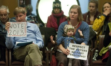 Mel Rader, a co-director of Upstream Public Health and a fluoride advocate, sits next to Angel Lambart and her daughter in December. After opponents collected enough signatures to force a fluoride vote, the Portland City Council fast-tracked it to the May 21 election instead of 2014.