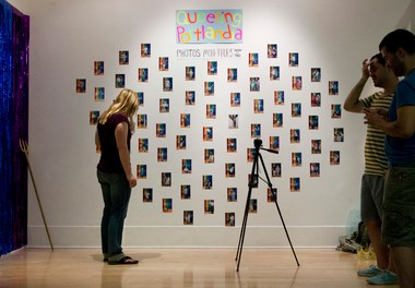 July 30, 2013 - Sarah Silliman looks over the makeshift gallery of photos set up in the lobby of the Portland Building Tuesday afternoon.