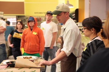 New Seasons Meat and Seafood Manager David Real leads a training for new workers at its North Williams Avenue store. Here, he shows the new hires how to correctly package sausage.