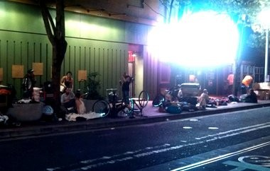 Homeless people sit on the sidewalk outside Star Theater on the night of a show. Co-owner Paul Park says the prospect of walking through people to get to the door deterred would-be customers.