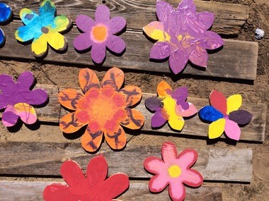 Children and adults painted wooden flowers at the April plant sale and raffle. Vicki Wilson plans to hang the flowers on the fence to discourage people from climbing into the lot.