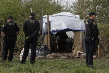 Portland Police officers surveyed an unauthorized campsite just off the Springwater Corridor in east Portland in late April.
