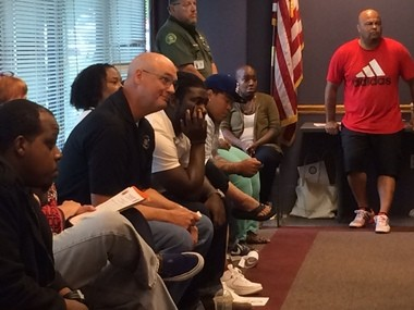 North Precinct police Cmdr. Mike Leloff, seated wearing black shirt and glasses, praised members of the community for working to keep Thursday night's local protest about the Ferguson police shooting peaceful.