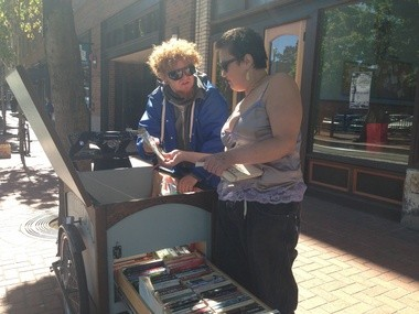 Street librarian Redd Moon helps a reader make a selection.