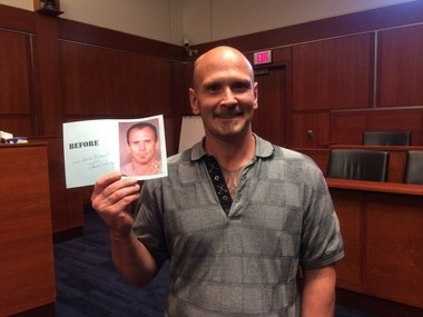 Richard Pitts shows his graduation card with one of his previous mugshots.