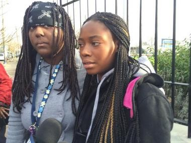 "Anita Irakoze,17, right, was outside buying snacks. She said, ""I heard the gunshots and started running for my life."" She said she heard four shots. On the left, Quennie Hillman said her cousin was one of the boys who were shot. She was inside school and heard four shots."
