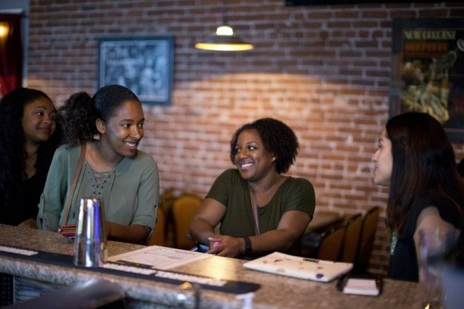 Stephanie Ghoston, center, and her partner, Maxime Paul, recently moved to Portland from Washington, D.C. They gathered a group of new friends together recently at Solae's, a black-owned jazz club on Northeast Alberta Street in Portland. August 4, 2016. Beth Nakamura/Staff